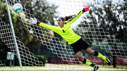 A teenage goalie dives to her right to save a soccer ball from going into the net
