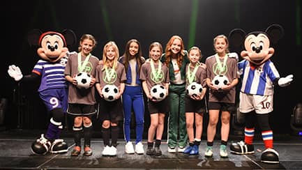 Mickey Mouse and Minnie Mouse, dressed in soccer uniforms, stand on opposite ends of a line of girls wearing medals and holding soccer balls