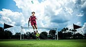 A soccer player jumping for a ball while a goalie stands behind him