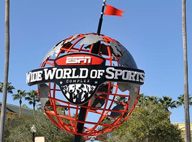 A large globe with a logo for ESPN Wide World of Sports Complex sits between two palm trees