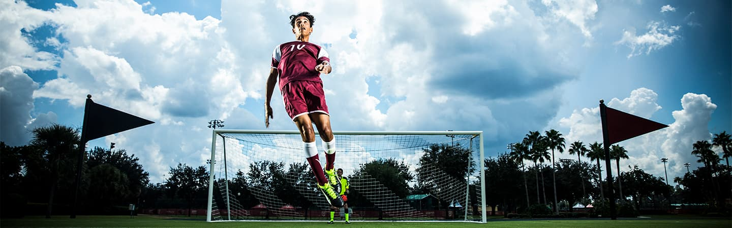 A male soccer player jumps in the air towards a ball high above him as a goalie looks on from in the goal
