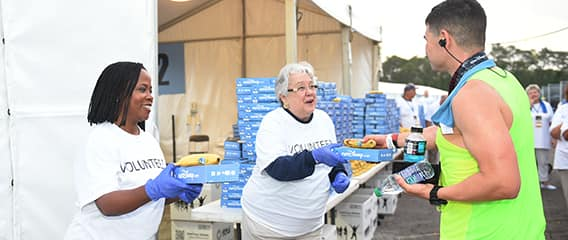 Outside the food tent, a volunteer hands a boxed meal and banana to a passing runner with other volunteers standing nearby