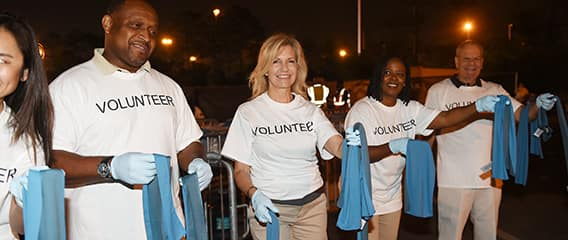 A line of smiling volunteers holds out towels for race runners to grab while passing by