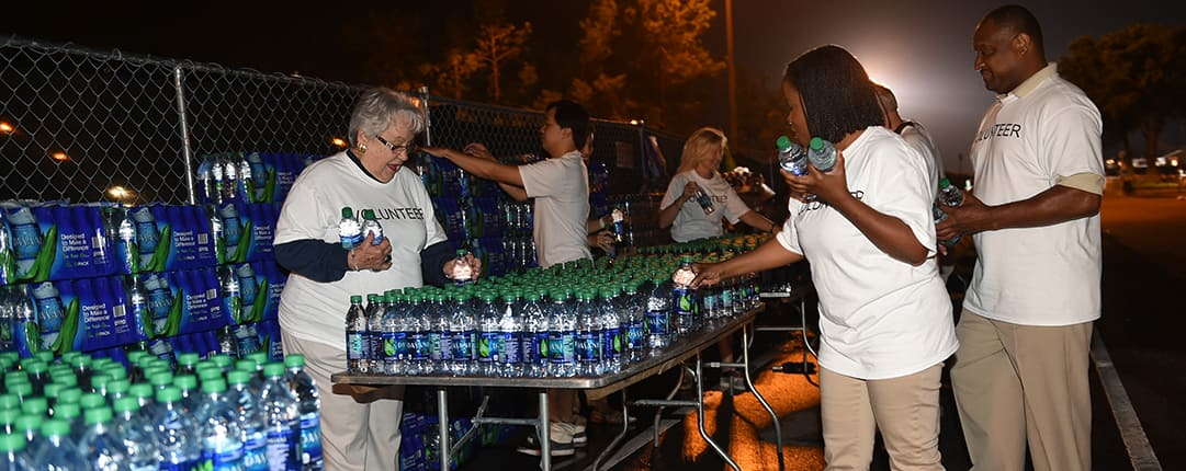 Before sunrise, volunteers line a table with water bottles for the race runners