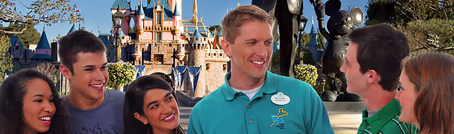 A Cast Member with smiling young adults by the Sleeping Beauty Castle