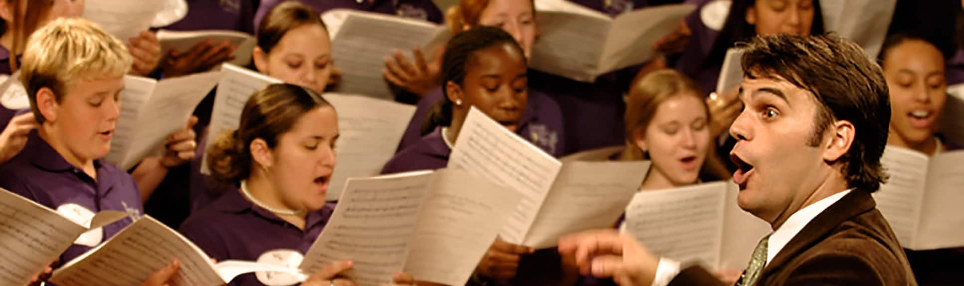 A conductor directing a group of young choir performers holding sheet music