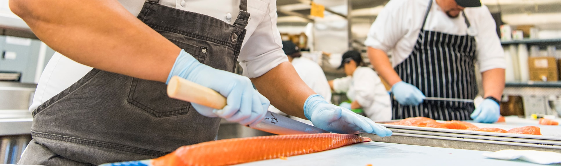 Cooks slice fish and work in a kitchen
