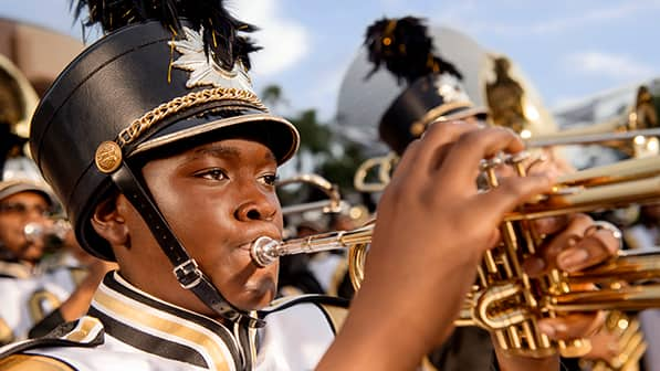 A band wearing uniforms and playing trumpets