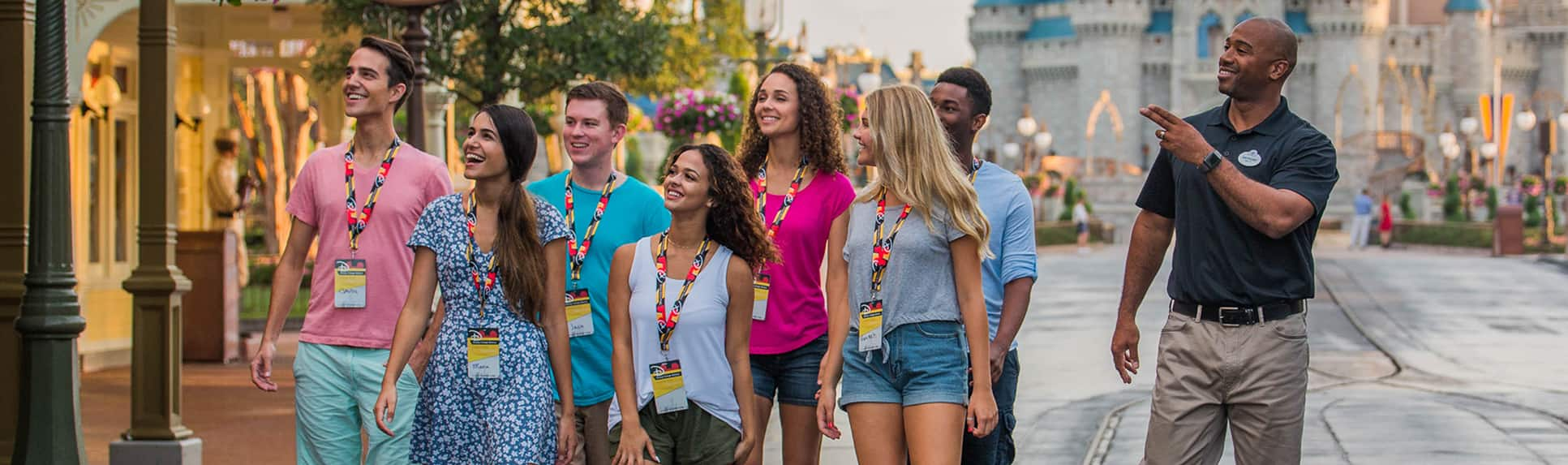 A Disney Cast Member leading a group of young adults through Magic Kingdom Park