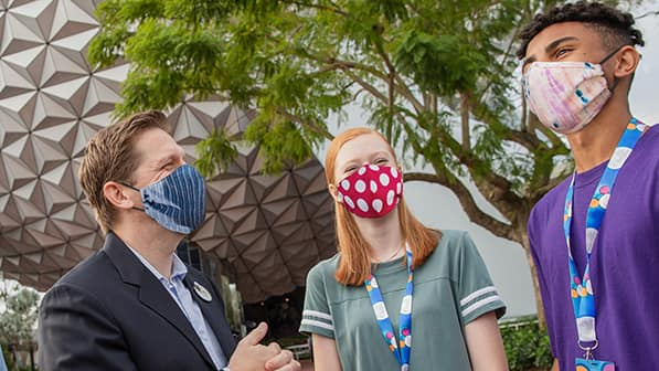 A male Cast Member wearing a mask talks with a teen girl wearing a polka dot mask and a teen boy wearing a tie dye mask in front of Spaceship Earth at Epcot