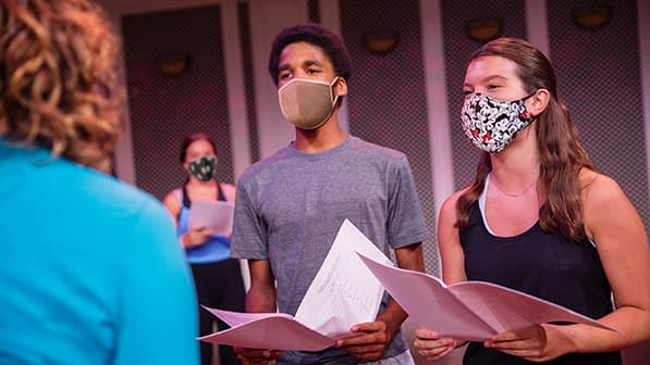 A boy wearing a mask, a girl wearing a Minnie Mouse mask and girl wearing a mask in the background, hold open booklets and face a woman