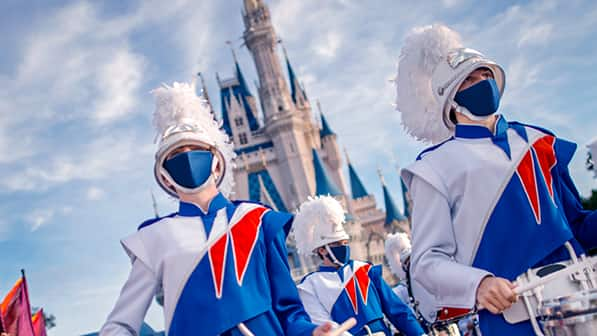 Drummers in a marching band wear matching masks and uniforms as they perform in front of Cinderella Castle at Magic Kingdom Park at Walt Disney World Resort
