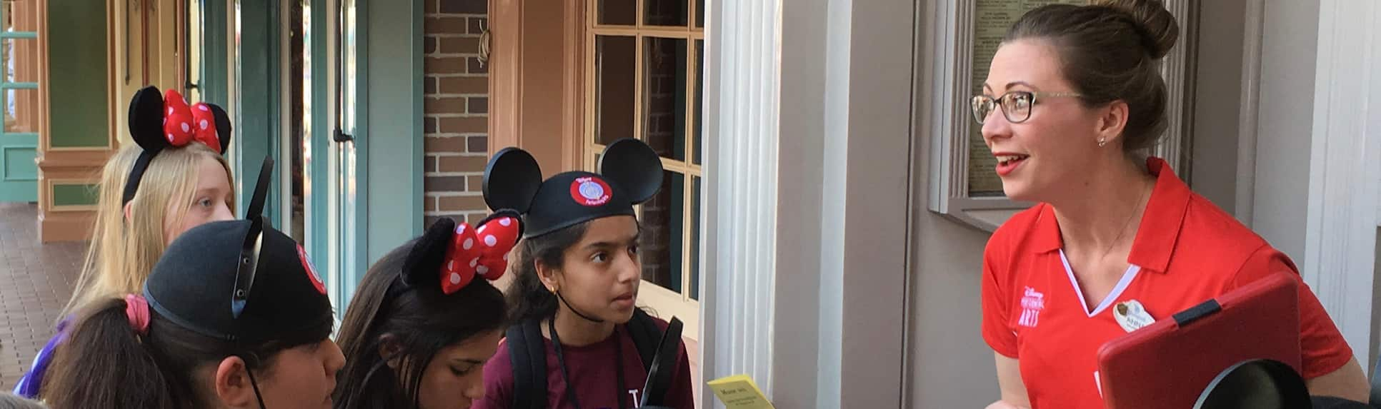 A Cast Member speaking to a small group of preteens wearing Mickey ears