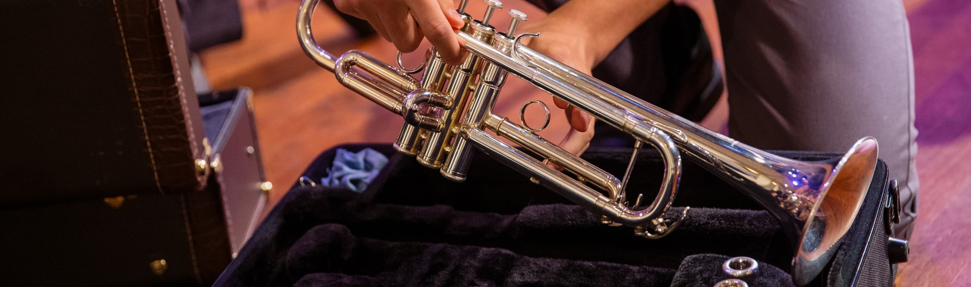 A young man putting his trumpet into a case