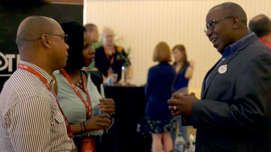A Disney Cast Member in business attire talking with two Summit participants at a networking event